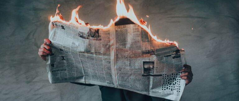 World events causing a newspaper to burst into flames while someone reads it. Surreal blog post image.